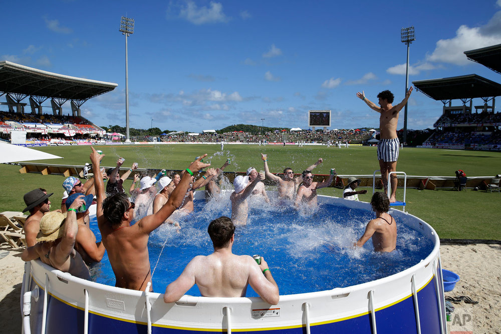 England cricket fans watch the first day of the second Test cricket match against West Indies, from a pool at the Sir Vivian Richards Stadium in North Sound, Antigua and Barbuda, Jan. 31, 2019. (AP Photo/Ricardo Mazalan)