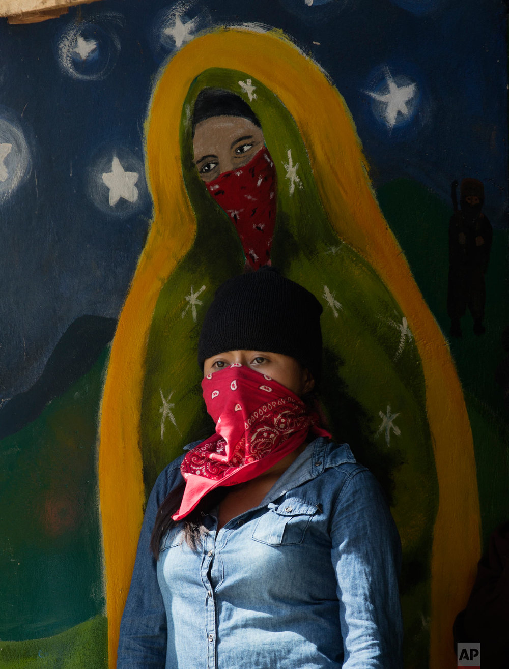 A masked, female member of the Zapatista National Liberation Army (EZLN) stands by a mural depicting a masked version of the Virgin of Guadalupe, at an event marking the 25th anniversary of the Zapatista uprising in La Realidad, Chiapas, Mexico, Jan. 1, 2019. (AP Photo/Eduardo Verdugo)