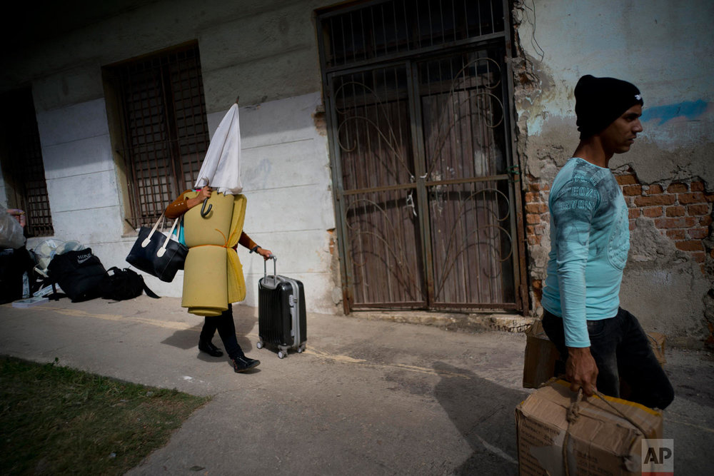 People left homeless by a tornado carry their belongings to a bus as they move to a shelter in Havana, Cuba, Jan. 28, 2019. (AP Photo/Ramon Espinosa)