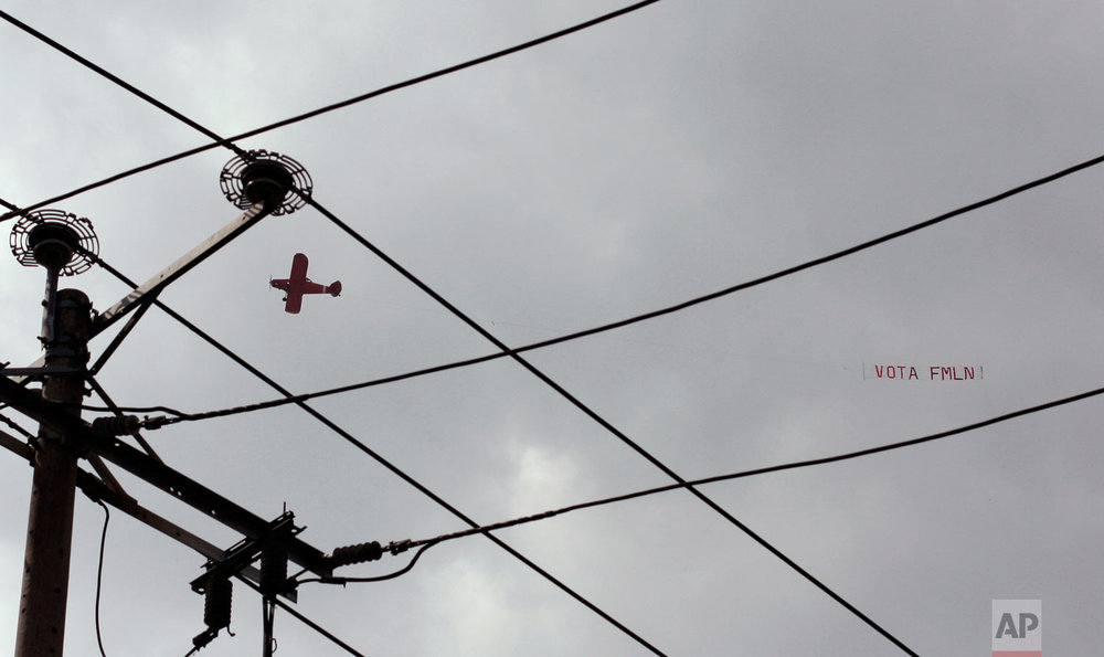 """An airplane flies a banner that reads in Spanish """"Vote for the FMLN"""" over a closing presidential campaign rally in San Salvador, El Salvador, Jan. 27, 2019, ahead of the presidential election. FMLN lost to Nayib Bukele with the GANA — the Grand Alliance for National Unity party. (AP Photo/Salvador Melendez)"""