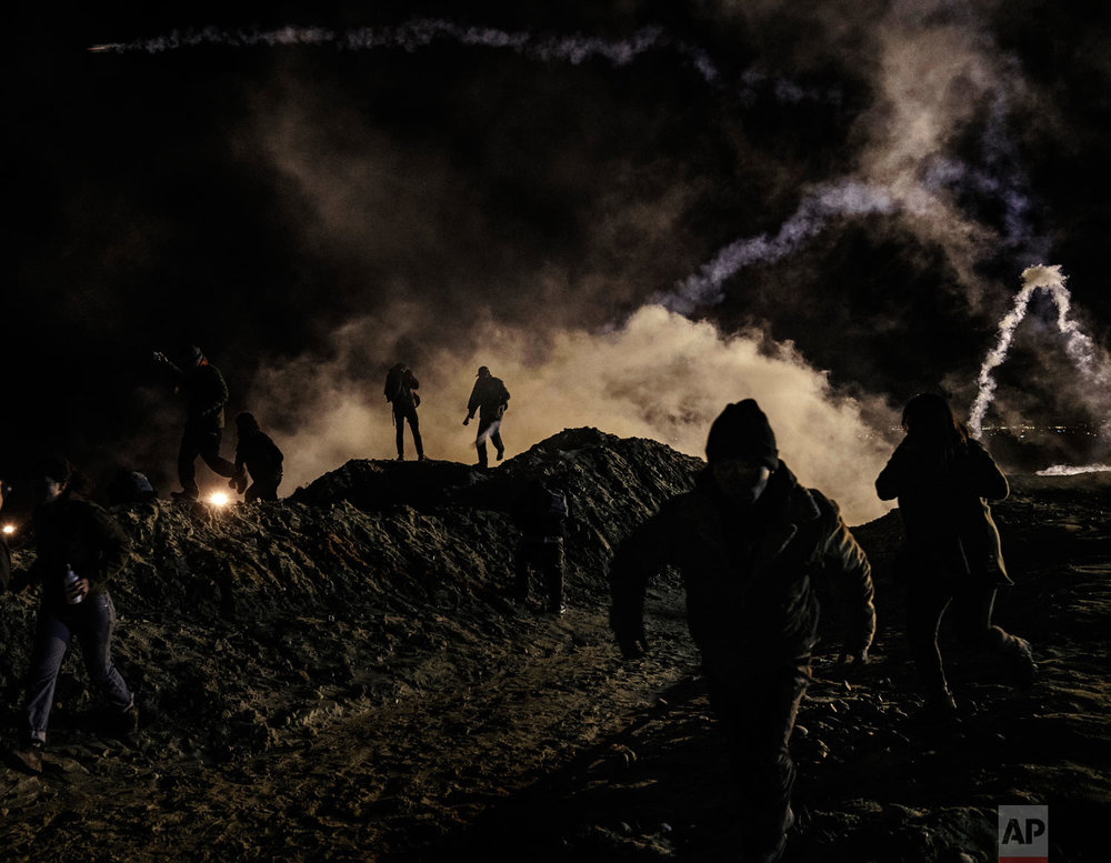 Migrants run from tear gas fired by U.S. Border Protection agents after they climbed the fence in an attempt to enter San Diego, Calif., from Tijuana, Mexico, Jan. 1, 2019. (AP Photo/Daniel Ochoa de Olza)