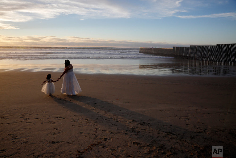 Ileze Dariel, of Tijuana, Mexico, reaches for the hand of her daughter Jimena as they wait for a photographer while taking family pictures on the beach next to the border wall, right, Jan. 9, 2019, in Tijuana, Mexico. (AP Photo/Gregory Bull)