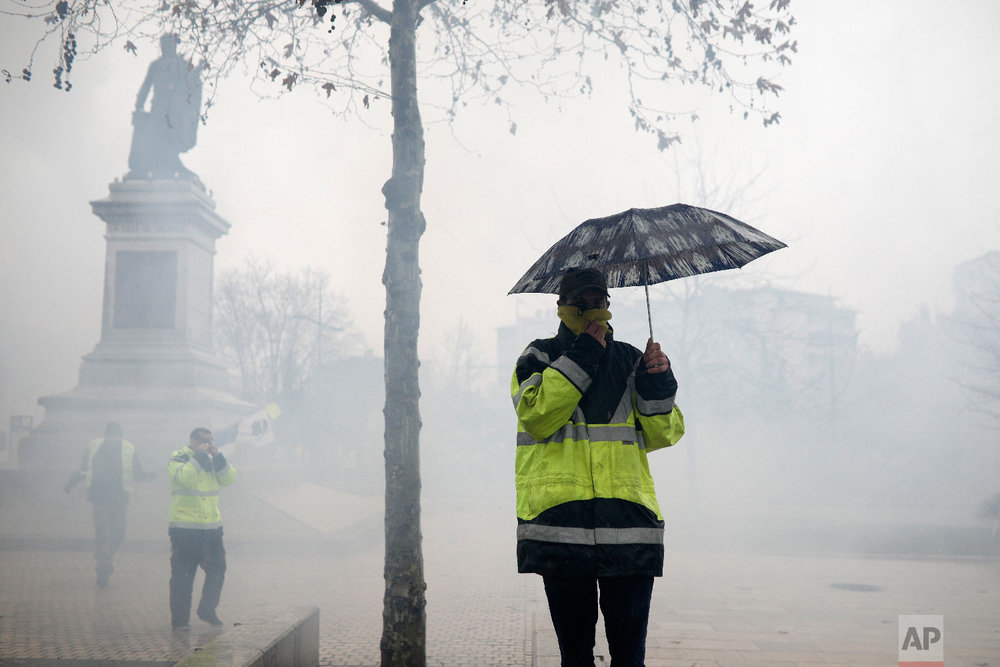 Yellow vests protestors protect themselves from tear gas during scuffles Saturday, Feb. 2, 2019, in Valence, central France. (AP Photo/Kamil Zihnioglu)
