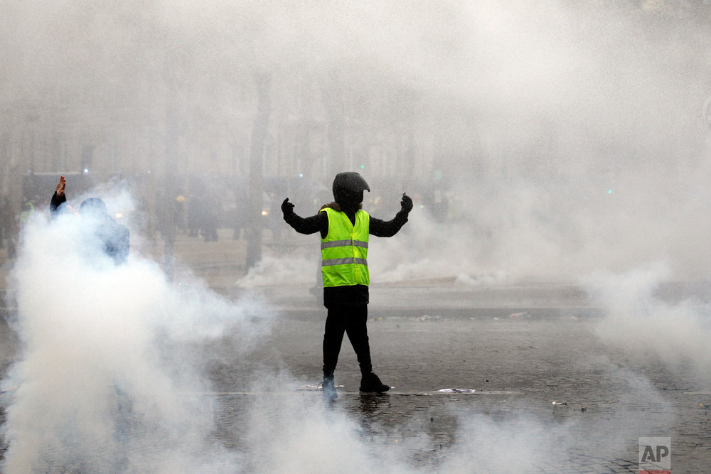 A yellow vest protester taunts riot police during clashes around the Arc of Triomphe in Paris, France, Jan. 12, 2019. (AP Photo/Kamil Zihnioglu)