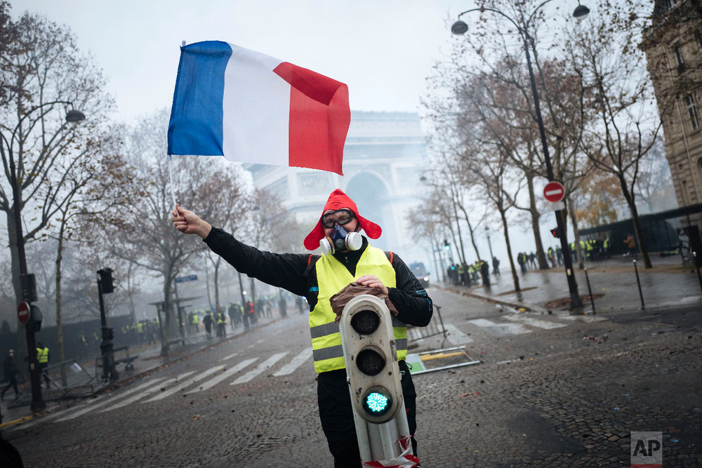 A demonstrator holds a French flag near the Arc de Triomphe during a demonstration, Dec.1, 2018 in Paris. (AP Photo/Kamil Zihnioglu)