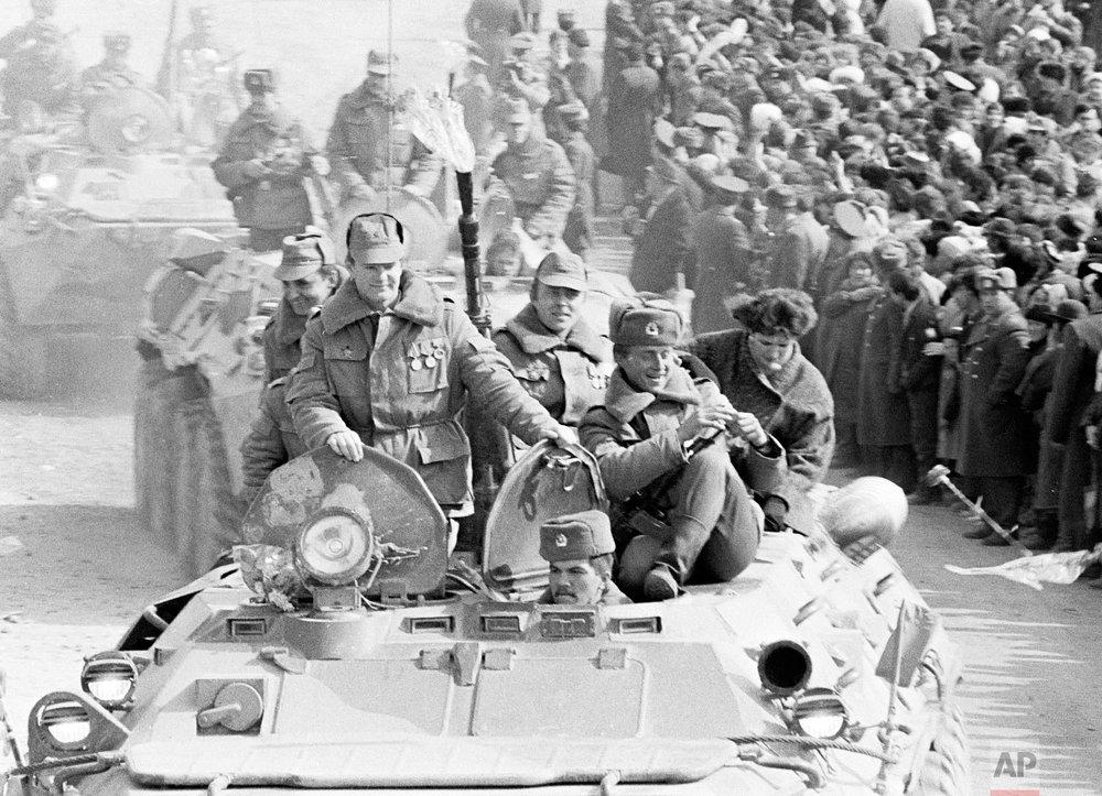 Soviet Army soldiers ride armored personnel carriers after their unit crossed a bridge on the border between Afghanistan and then Soviet Uzbekistan near the Uzbek town of Termez, Uzbekistan on Feb. 15, 1989. (AP Photo/Alexander Zemlianichenko)