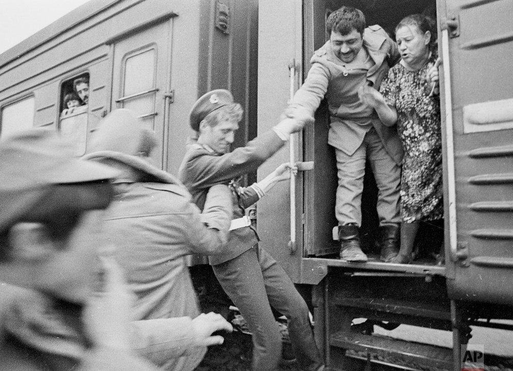 Soviet Army soldiers help each other to catch a train home after crossing a bridge on the border between Afghanistan and then Soviet Uzbekistan near the Uzbek town of Termez, Uzbekistan Feb. 15, 1989. (AP Photo/Alexander Zemlianichenko)