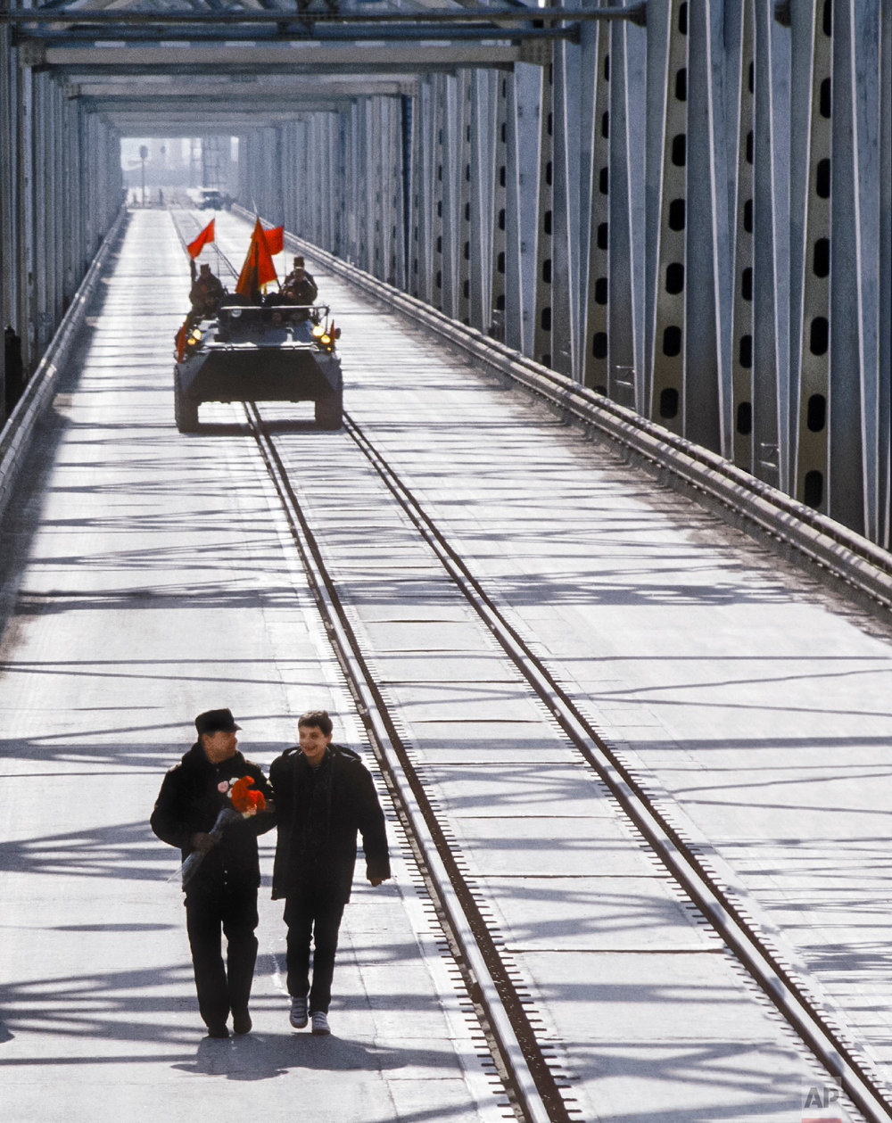 Lt. Gen. Boris Gromov, left, with his son Maxim, walk across a bridge over the Amy Darya River, at Termez, Uzbekistan on Feb. 15, 1989. (AP Photo/Vyacheslav Kiselev)