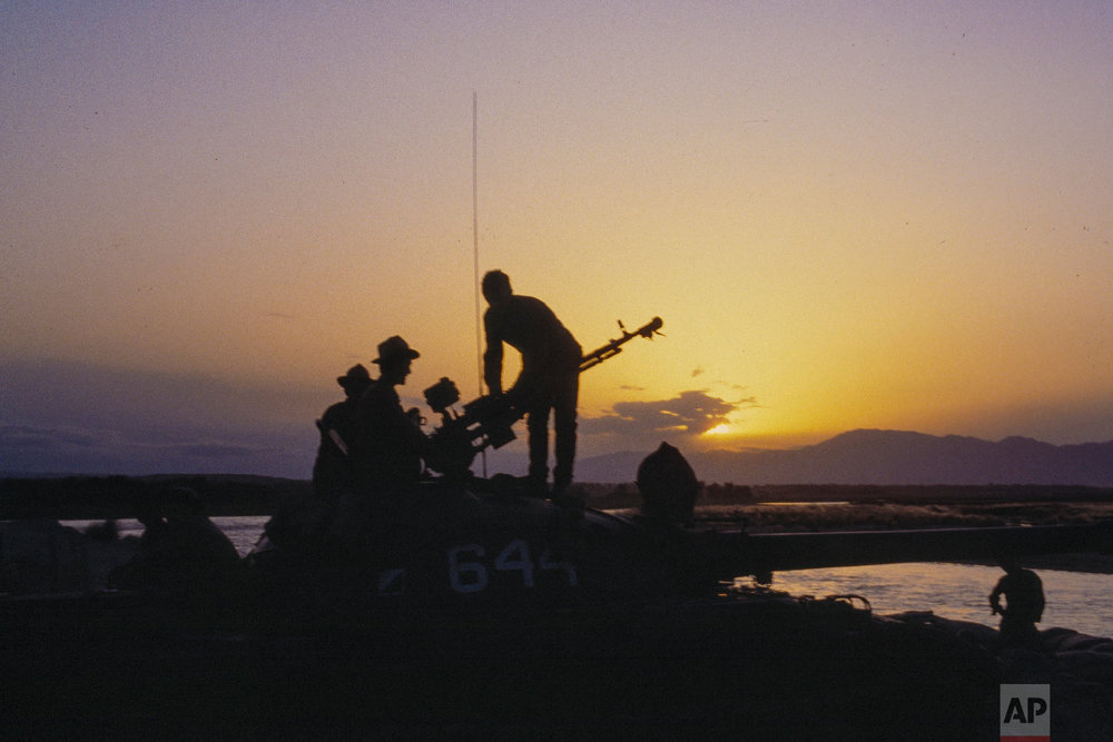 Soviet Army soldiers stand atop of a tank at a outpost during sunset in Afghanistan on September 1984. (AP Photo/Alexander Zemlianichenko)
