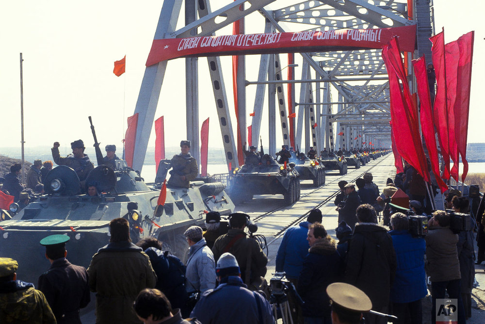Soviet Army soldiers wave their hands as their unit crosses a bridge on the border between Afghanistan and then Soviet Uzbekistan near the Uzbek town of Termez, Uzbekistan on Feb. 15, 1989. (Leonid Yakutin/Defense Ministry Press Service via AP)