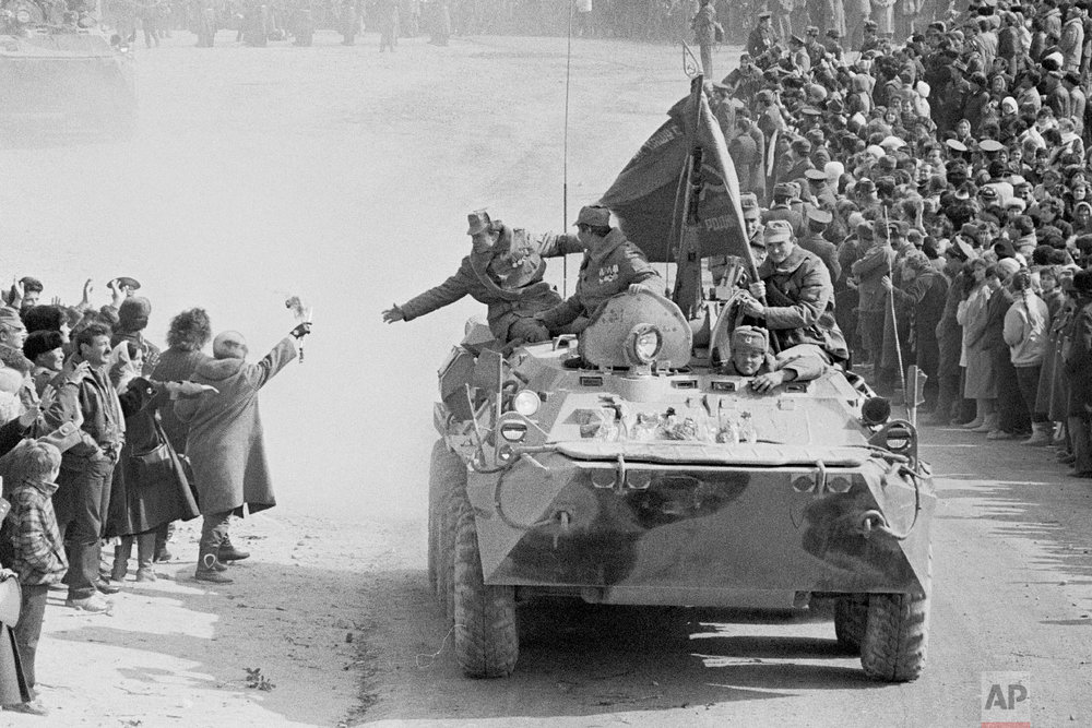 People and relatives greet Soviet Army soldiers driving on their armored personnel carriers after crossing a bridge on the border between Afghanistan and then Soviet Uzbekistan near the Uzbek town of Termez, Uzbekistan on Feb. 15, 1989. (AP Photo/Alexander Zemlianichenko)