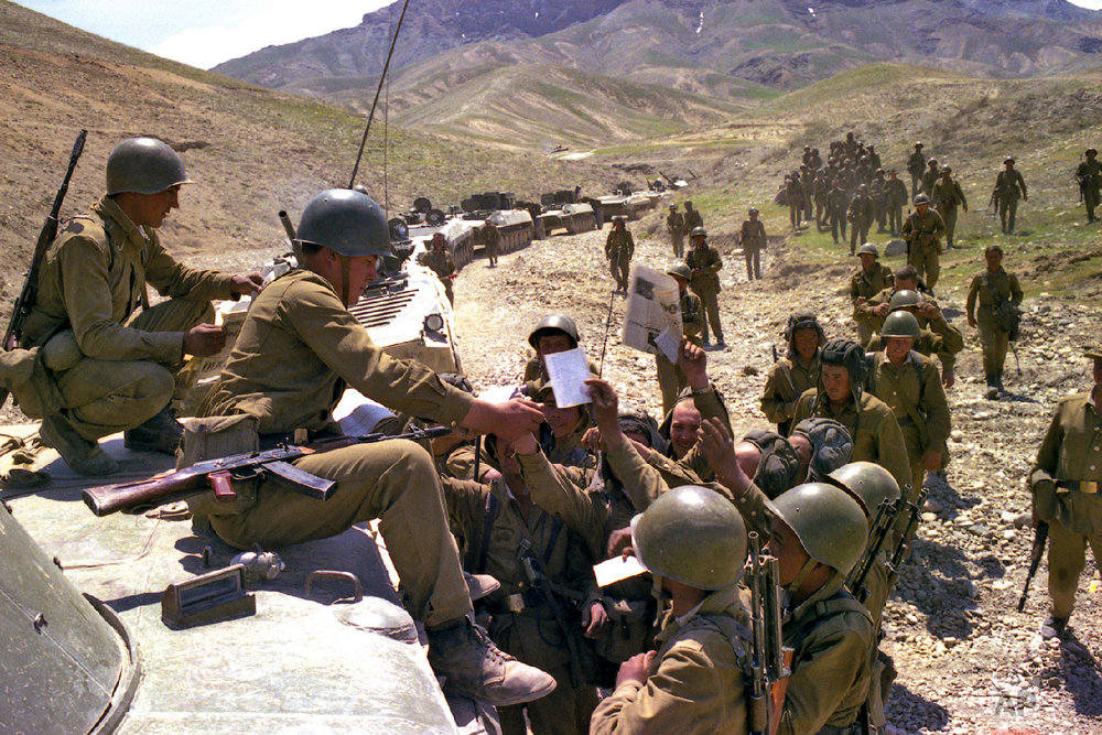 Soviet soldiers get fresh newspapers and mail while a convoy stoped somewhere in Afghanistan. (Leonid Yakutin/Defense Ministry Press Service via AP)