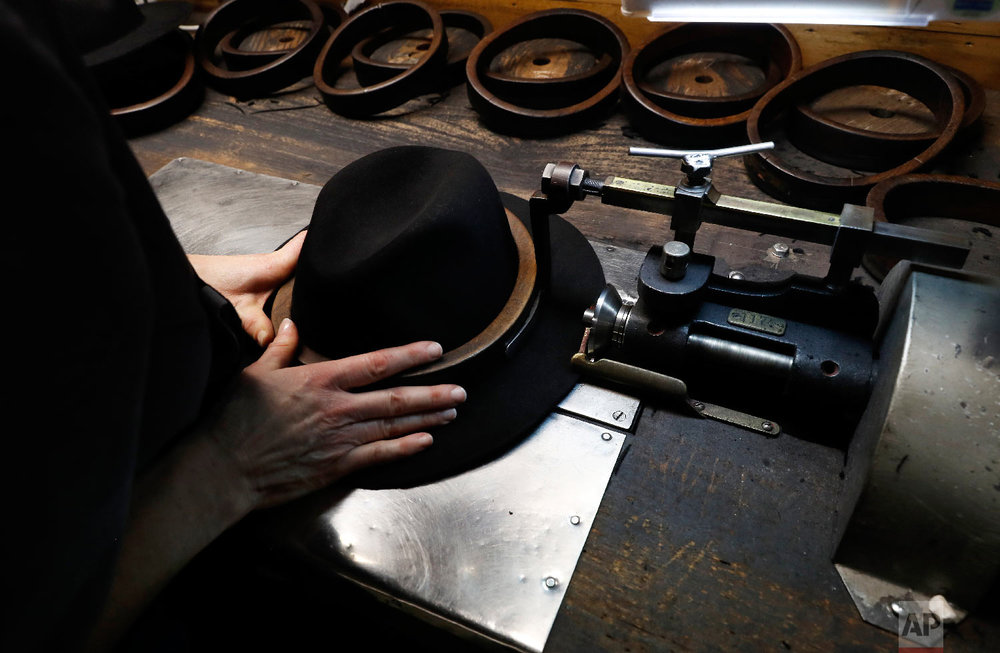 A man holds a hat inside the Borsalino hat factory, in Spinetta Marengo, near Alessandria, Italy, Thursday, Jan. 17, 2019. (AP Photo/Antonio Calanni)