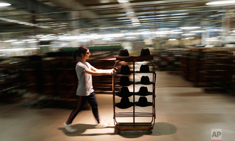 A woman worker pushes a cart with hats in Borsalino's hat factory, in Spinetta Marengo, near Alessandria, Italy, Thursday, Jan. 17, 2019. (AP Photo/Antonio Calanni)