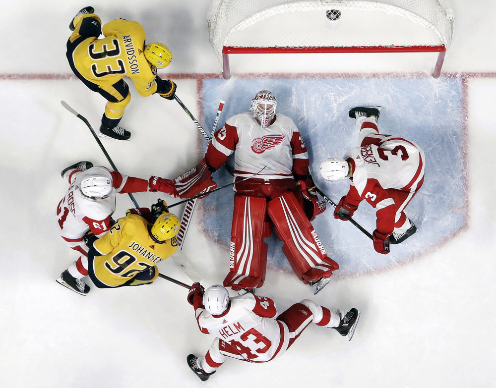 Detroit Red Wings goaltender Jimmy Howard (35) covers the puck during the third period of the team's NHL hockey game against the Nashville Predators on Tuesday, Feb. 12, 2019, in Nashville, Tenn. The Red Wings won 3-2. (AP Photo/Mark Humphrey)