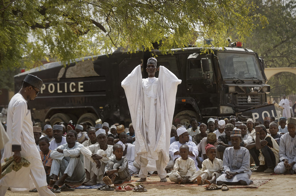 Muslims make traditional Friday prayers in front of a police riot truck, providing security due to the ongoing general threat of attacks by Islamic extremist group Boko Haram, at a mosque near the Emir's palace in Kano, northern Nigeria, Friday, Feb. 15, 2019. Nigeria is due to hold general elections on Saturday, pitting incumbent President Muhammadu Buhari against leading opposition presidential candidate Atiku Abubakar. (AP Photo/Ben Curtis)