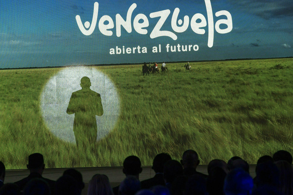 The shadow of Venezuela's Communications Minister Jorge Rodriguez is cast on a screen while presenting the country's strategy to promote tourism in all its regions, in the Hotel Alba Caracas, in Caracas, Venezuela, Monday, Feb. 11, 2019. (AP Photo/Rodrigo Abd)