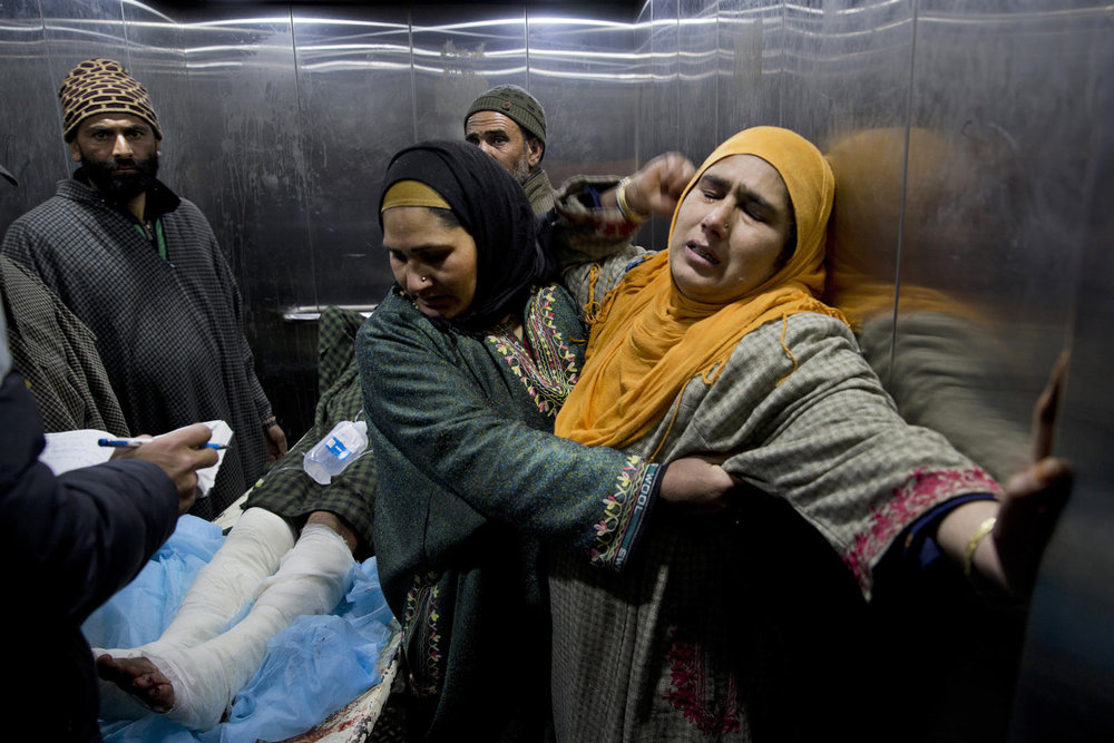 A Kashmiri woman is comforted by another as a young wounded relative is taken for treatment inside a hospital Srinagar Indian-controlled Kashmir, Wednesday, Feb. 13, 2019. Police and medics say at least 25 high school students have been injured by an explosion in their classroom in Indian-controlled Kashmir. (AP Photo/ Dar Yasin)