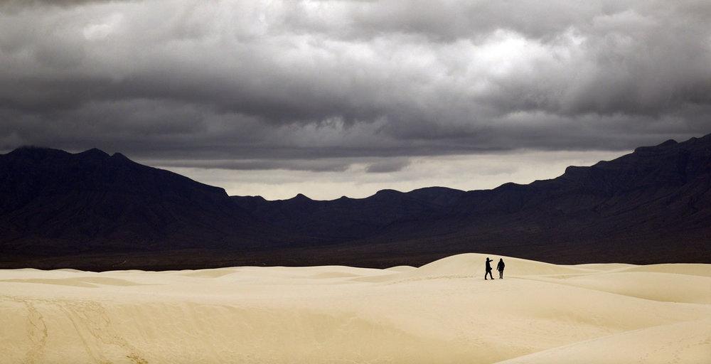 Visitors walk across dunes at White Sands National Monument as a rain storm passes, Sunday, Feb. 10, 2019, near Alamogordo, N.M. (AP Photo/Eric Gay)