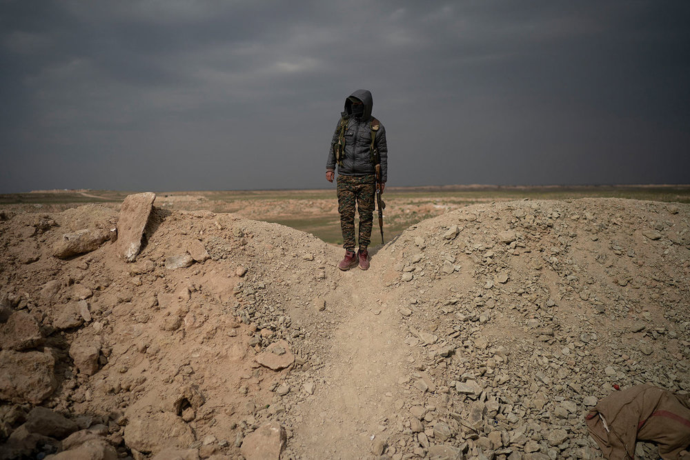A U.S.-backed Syrian Democratic Forces (SDF) fighter stands atop a hill in the desert outside the village of Baghouz, Syria, Thursday, Feb. 14, 2019. (AP Photo/Felipe Dana)
