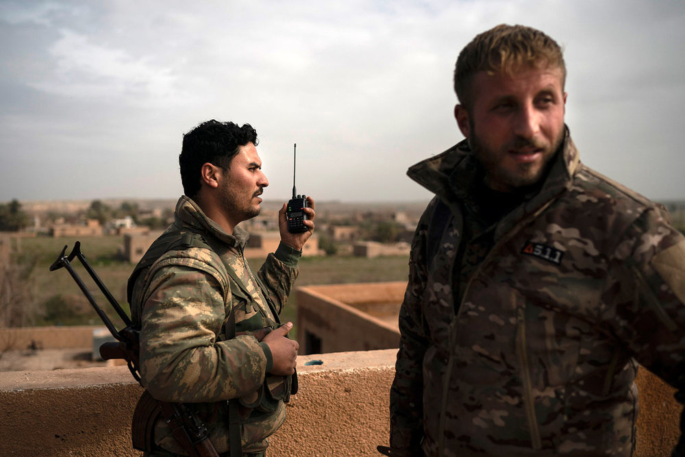 U.S.-backed Syrian Democratic Forces (SDF) fighters talk on a radio in a rooftop position as fight against Islamic State militants continues in the village of Baghouz, Syria, Saturday, Feb. 16, 2019. (AP Photo/Felipe Dana)