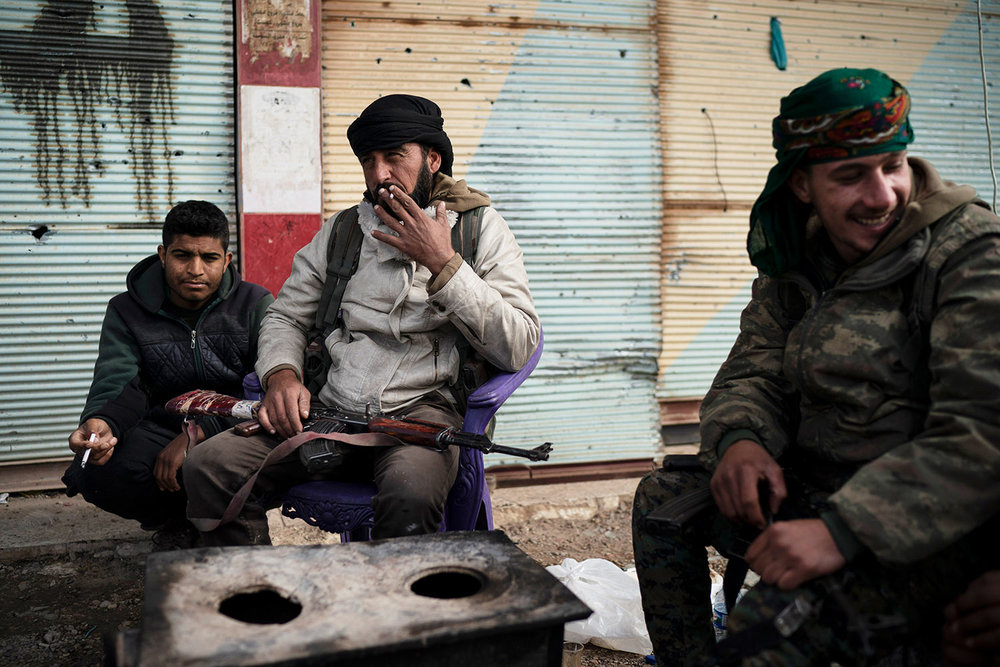 U.S.-backed Syrian Democratic Forces (SDF) fighters sit outside a building as fight against Islamic State militants continue in the village of Baghouz, Syria, Saturday, Feb. 16, 2019. (AP Photo/Felipe Dana)
