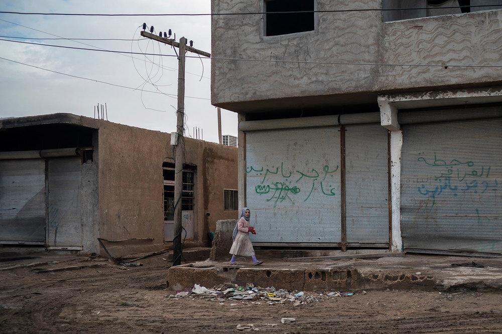 A girl walks in an area recently retaken by U.S.-backed Syrian Democratic Forces (SDF) from Islamic State militants in Hajin, Syria, Saturday, Feb. 16, 2019. (AP Photo/Felipe Dana)