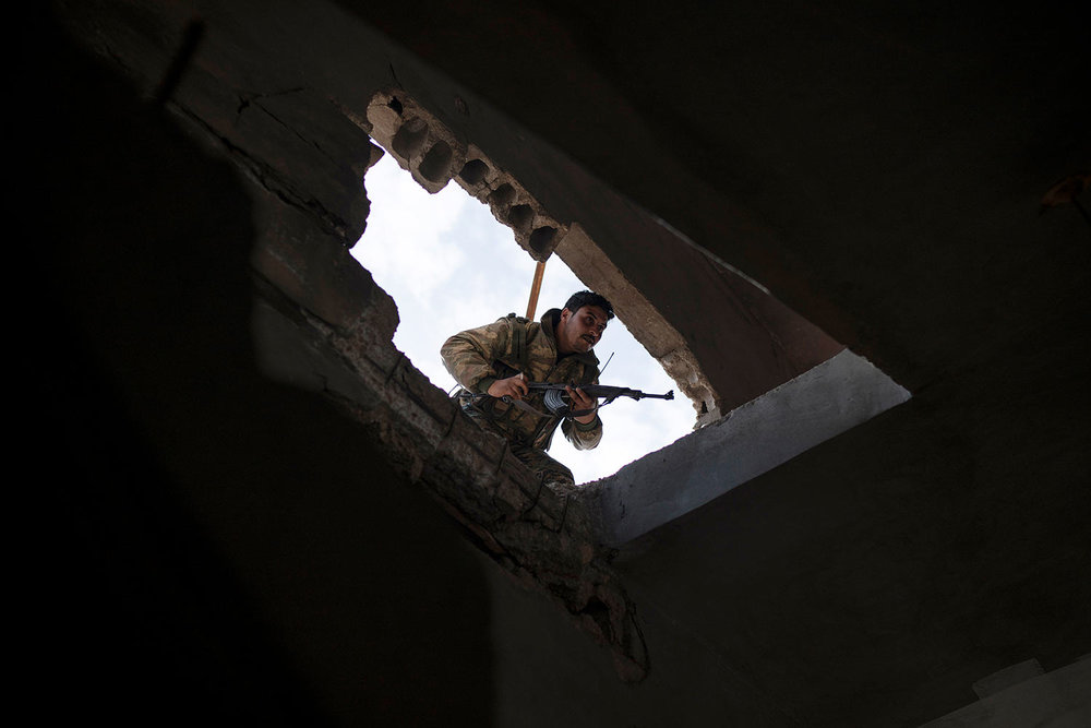 A U.S.-backed Syrian Democratic Forces (SDF) fighter enters a building as fight against Islamic State militants continues in the village of Baghouz, Syria, Saturday, Feb. 16, 2019. (AP Photo/Felipe Dana)