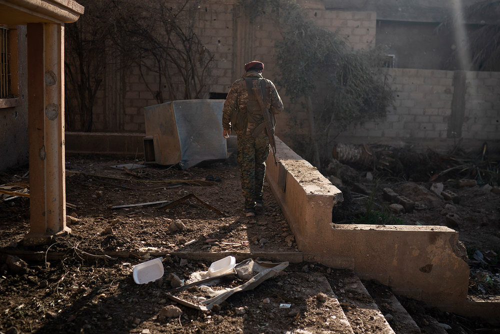 A U.S.-backed Syrian Democratic Forces (SDF) fighter walks near the last land still held by Islamic State militants in Baghouz, Syria, Monday, Feb. 18, 2019. Hundreds of Islamic State militants are surrounded in a tiny area in eastern Syria are refusing to surrender and are trying to negotiate an exit, Syrian activists and a person close to the negotiations said Monday. (AP Photo/Felipe Dana)