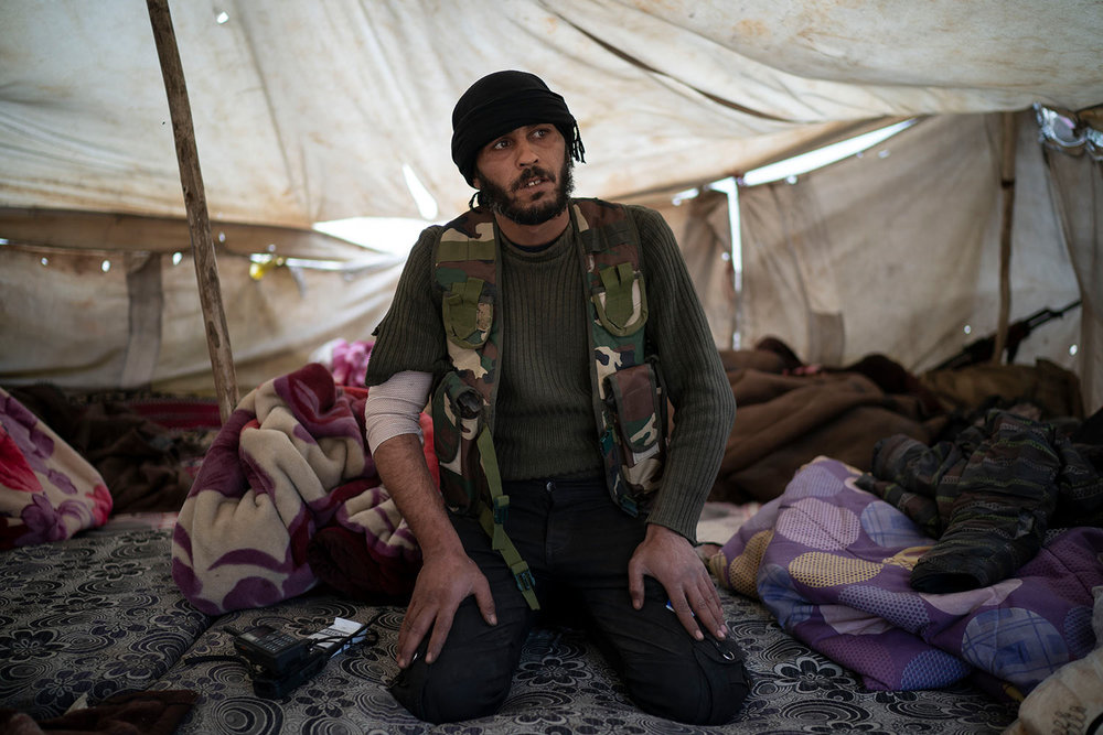 A U.S.-backed Syrian Democratic Forces (SDF) fighter sits inside a tent atop a hill in the desert outside the village of Baghouz, Syria, Thursday, Feb. 14, 2019. (AP Photo/Felipe Dana)