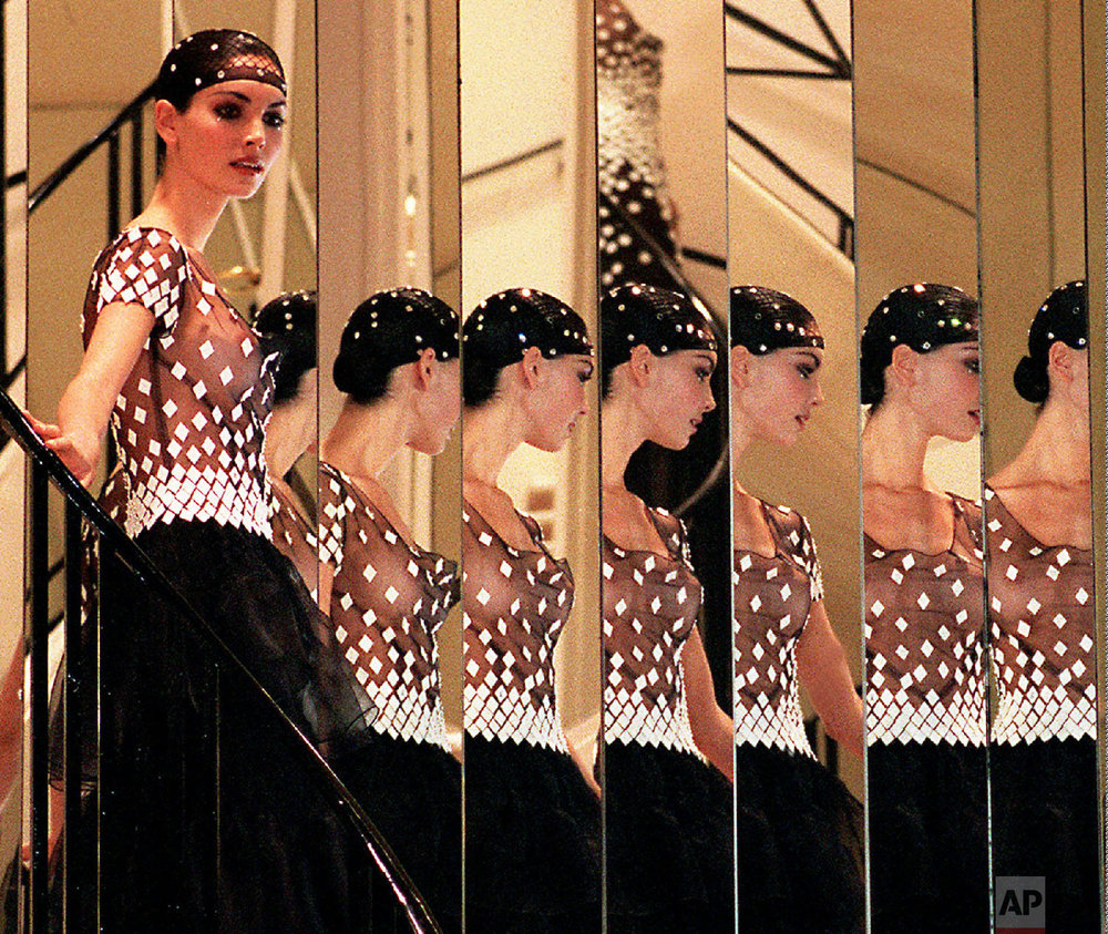 A model presents a black dress topped by a see-through strapless-brassiere reflected in mirrors during the presentation of the 1998 spring-summer haute couture collection of Chanel fashion house, designed by German Karl Lagerfeld, Jan.20, 1998, in Paris. (AP Photo/Laurent Rebours)