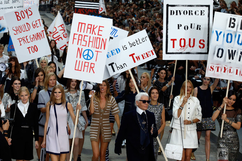 Models stage a fake demonstration, with German fashion designer Karl Lagerfeld, center right, as part of Chanel's Spring/Summer 2015 ready-to-wear fashion collection presented in Paris, France, Sept. 30, 2014. (AP Photo/Francois Mori)