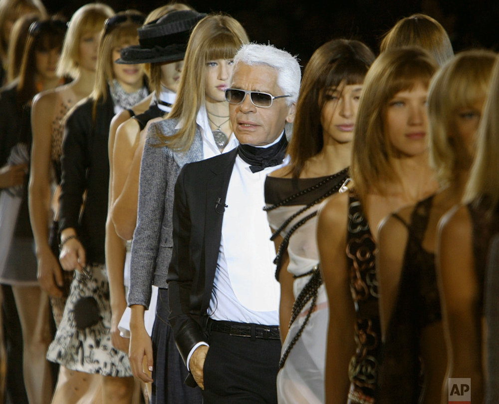 German fashion designer Karl Lagerfeld, center, joins his models on the catwalk after the presentation of the Spring-Summer 2003 ready-to-wear collection he designed for Chanel, Oct. 8, 2002 in Paris. (AP Photo/Michel Euler)