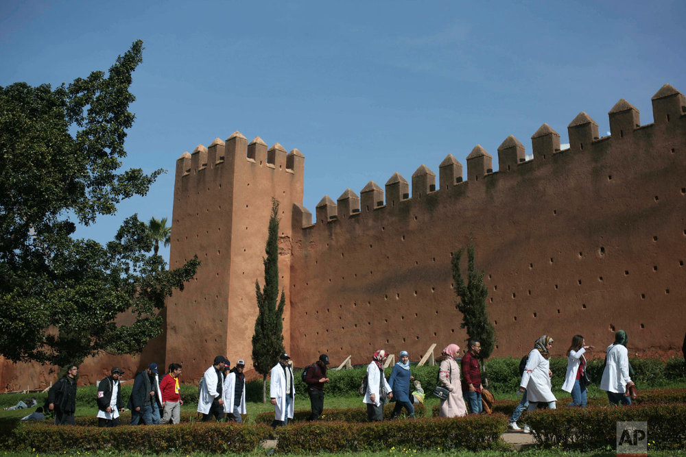 Protesting teachers walk past ancient walls in Rabat, Morocco, Feb. 20, 2019. (AP Photo/Mosa'ab Elshamy)