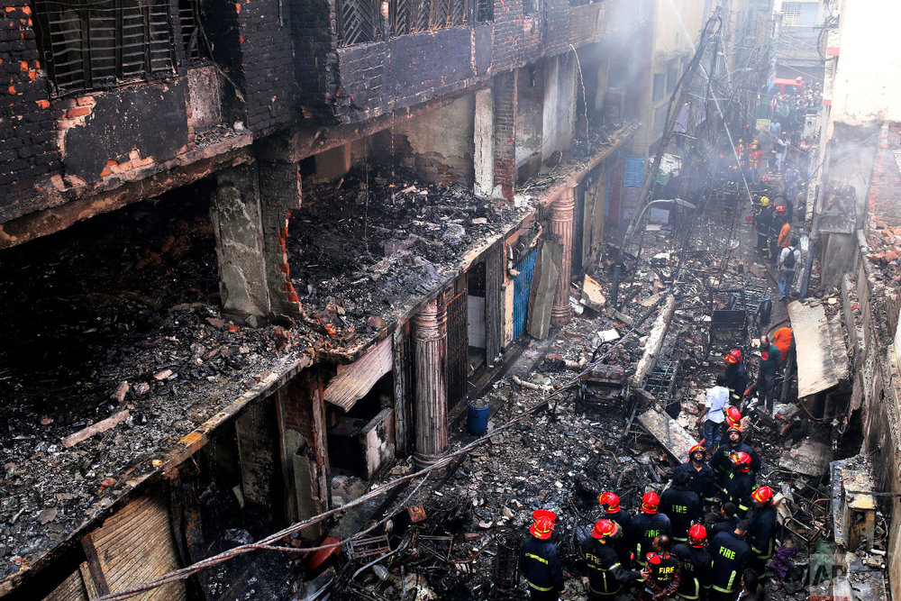Locals and firefighters gather around buildings that caught fire late Wednesday in Dhaka, Bangladesh, Thursday, Feb. 21, 2019. (AP Photo/Rehman Asad)