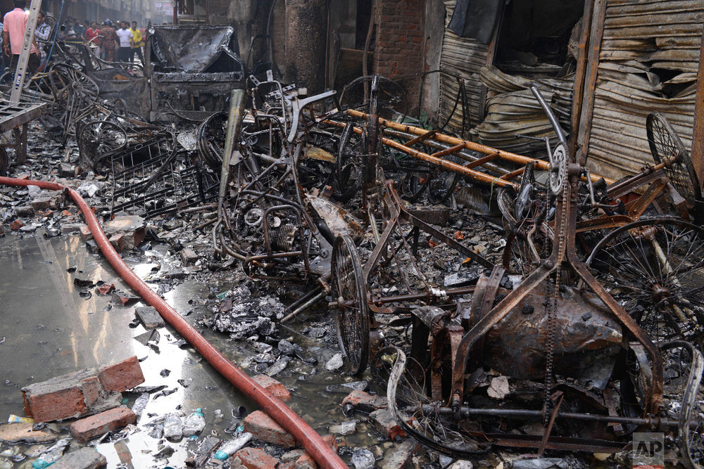 The wrangled and charred remains of rickshaws lie at the site of a late Wednesday night fire in Dhaka, Bangladesh, Thursday, Feb. 21, 2019. (AP Photo/Mahmud Hossain Opu )