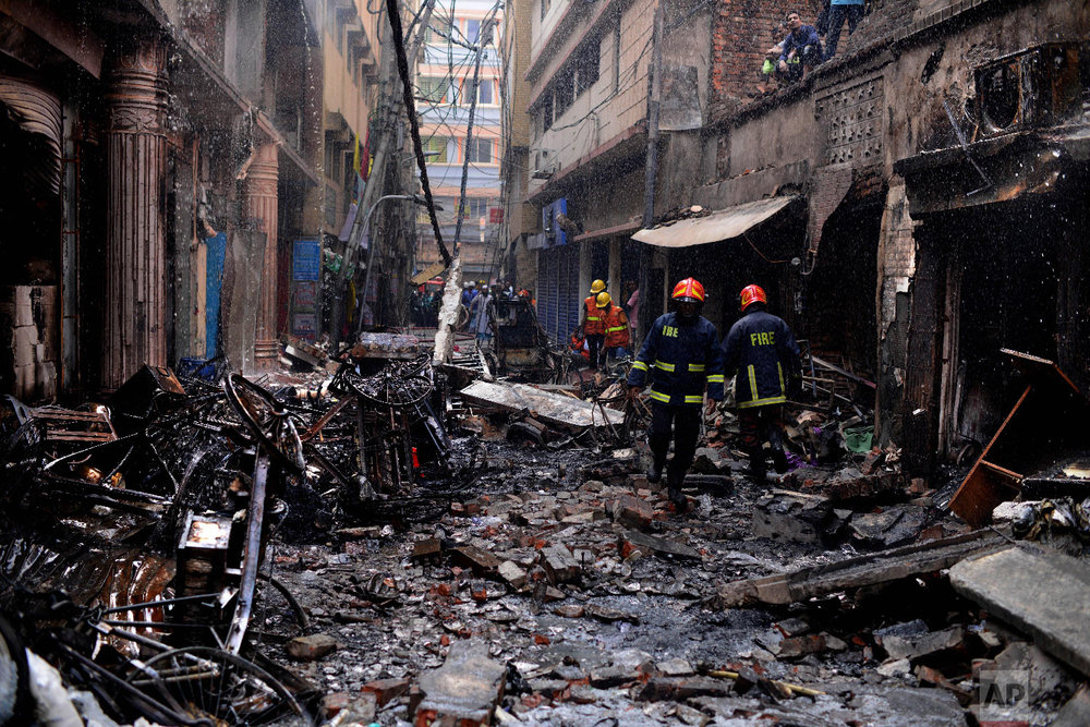 Firefighters gather around buildings that caught fire late Wednesday night in Dhaka, Bangladesh, Thursday, Feb. 21, 2019. (AP Photo/Mahmud Hossain Opu)