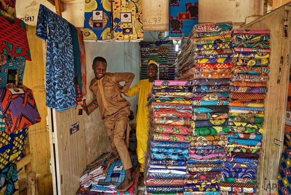 In this photo taken Tuesday, Feb. 19, 2019, shopkeepers stand by stacks of the wax-printed fabric made in China that fills the market in Kano, northern Nigeria. (AP Photo/Ben Curtis)