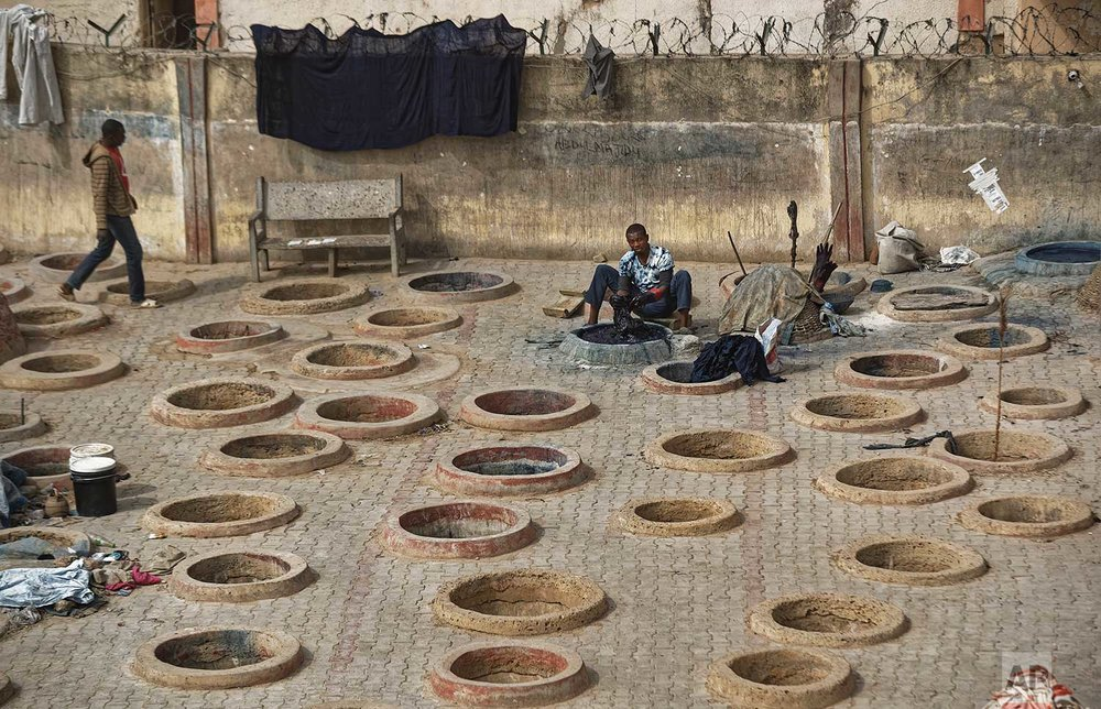 In this photo taken Tuesday, Feb. 19, 2019, a craftsman dyes cloth with indigo in one of the ancient dye pits of Kofar Mata in Kano, northern Nigeria. (AP Photo/Ben Curtis)