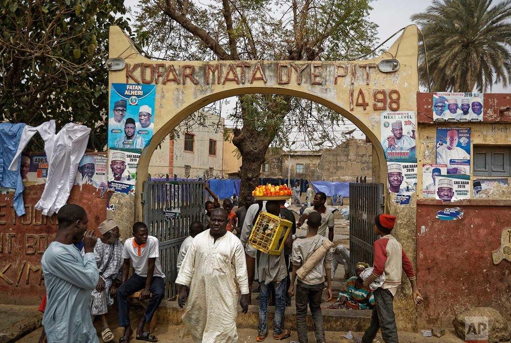 In this photo taken Tuesday, Feb. 19, 2019, Nigerians walk through the busy entranceway to the ancient dye pits of Kofar Mata in Kano, northern Nigeria. (AP Photo/Ben Curtis)