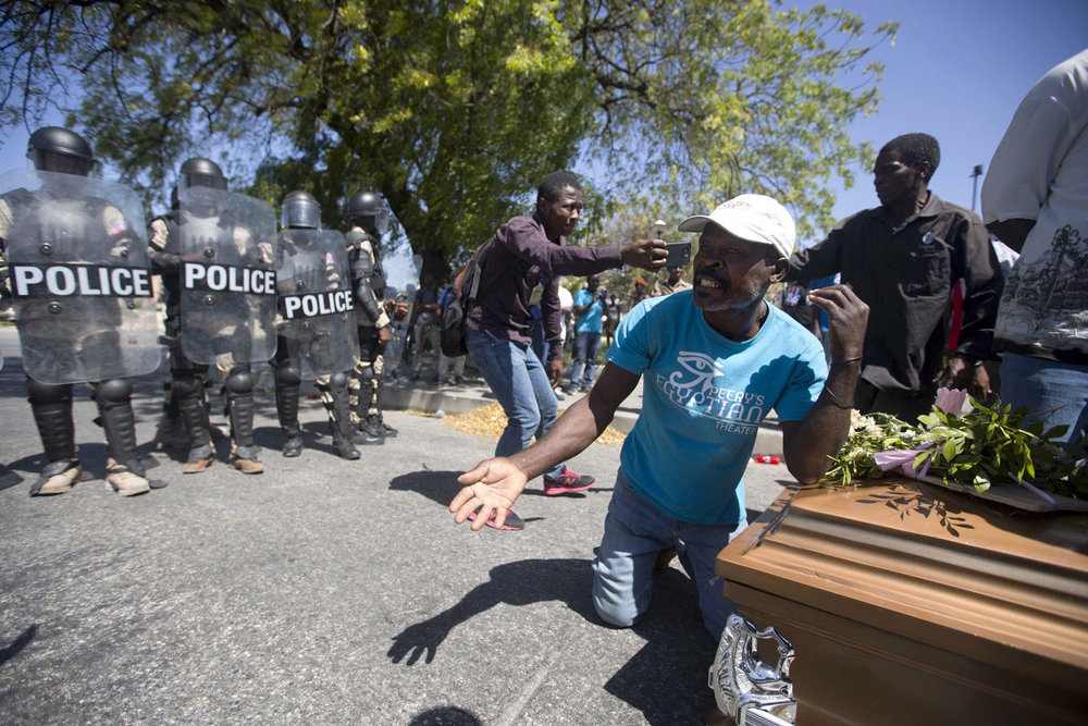 Demonstrators arrive in front of the National Palace carrying a coffin containing the body of a protester who was killed during the week's previous protests, as national police stop them, in Port-au-Prince, Haiti, Friday, Feb. 22, 2019. Protesters are angry about skyrocketing inflation and the government's failure to prosecute embezzlement from a multi-billion Venezuelan program that sent discounted oil to Haiti. (AP Photo/Dieu Nalio Chery)