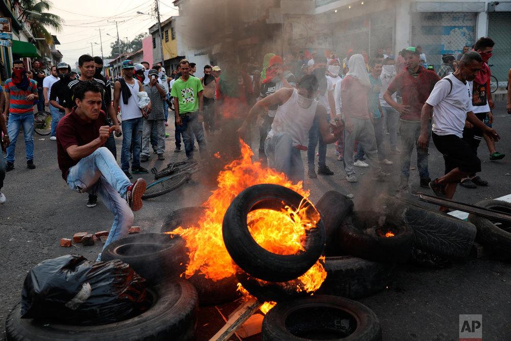 Demonstrators set up a burning barricade during clashes with the Venezuelan Bolivarian National Guard in Urena, Venezuela, near the border with Colombia, Saturday, Feb. 23, 2019. (AP Photo/Rodrigo Abd)