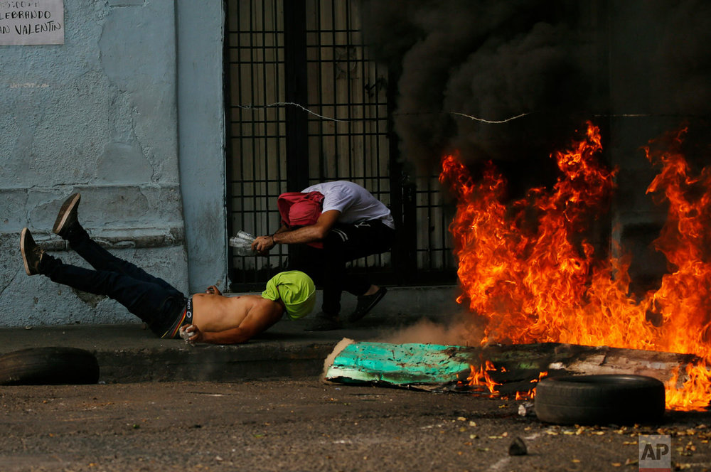 A demonstrator falls after getting caught by barbed wire during clashes with the Venezuelan Bolivarian National Guard in Urena, Venezuela, near the border with Colombia, Saturday, Feb. 23, 2019. (AP Photo/Fernando Llano)