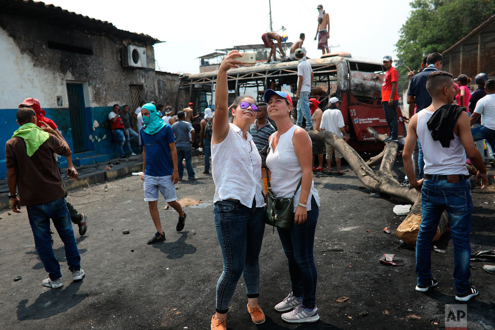 Opposition demonstrators take a selfie at the site where a torched bus is used as a barricade, during clashes with the Venezuelan Bolivarian National Guard in Urena, Venezuela, near the border with Colombia, Saturday, Feb. 23, 2019. (AP Photo/Rodrigo Abd)