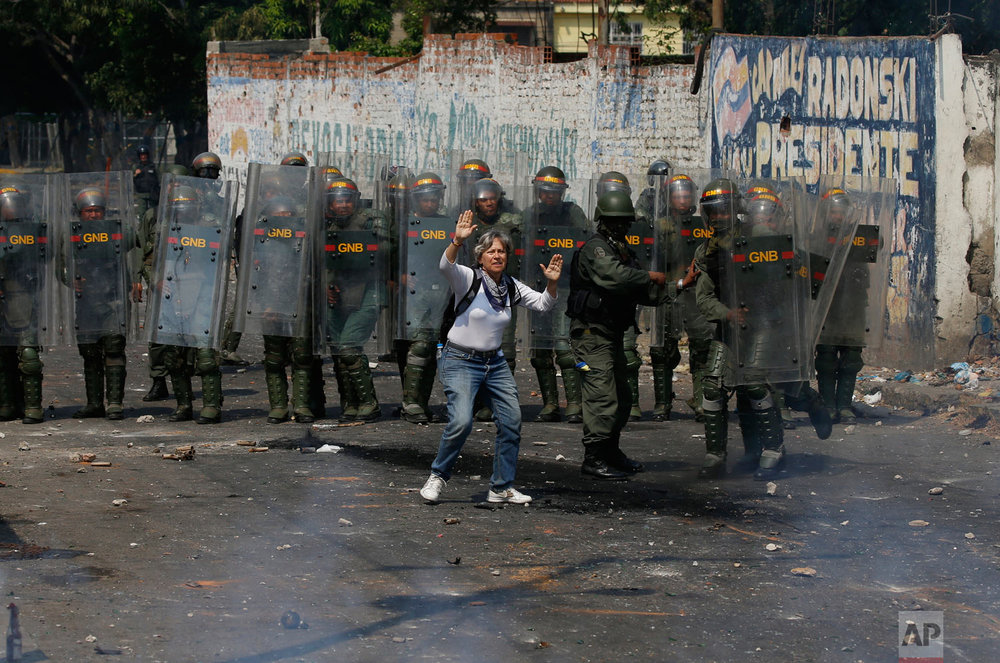 A demonstrator tries to stop the violence as she stands in front of a line of Venezuelan Bolivarian National Guard officers during clashes in Urena, Venezuela, near the border with Colombia, Saturday, Feb. 23, 2019. (AP Photo/Fernando Llano)