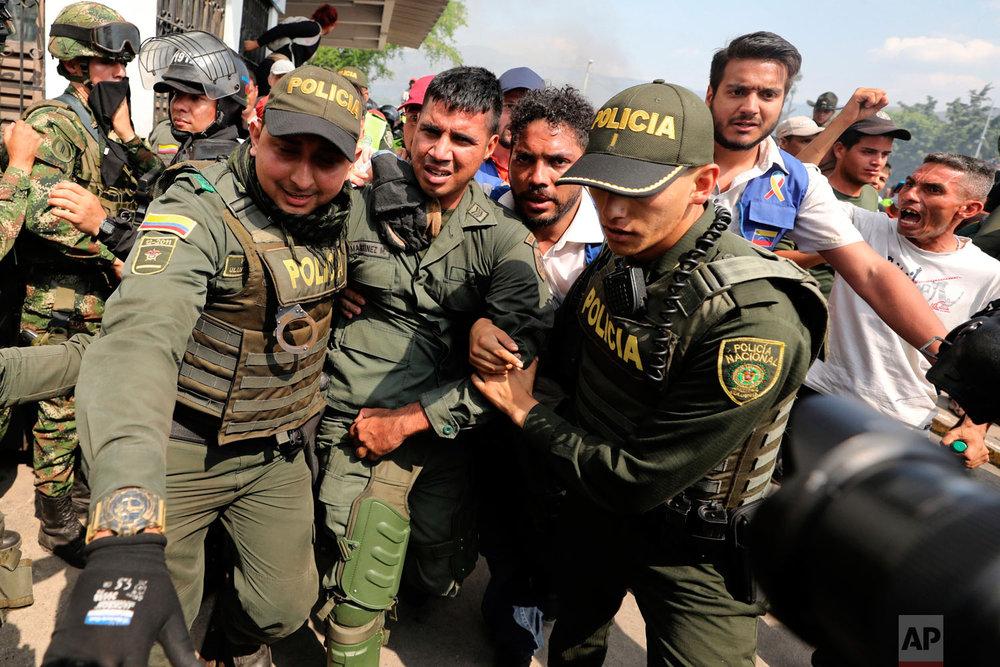 Colombian police escort a Venezuelan soldier who defected at the Simon Bolivar international bridge in Cucuta, Colombia, Saturday, Feb. 23, 2019. (AP Photo/Fernando Vergara)