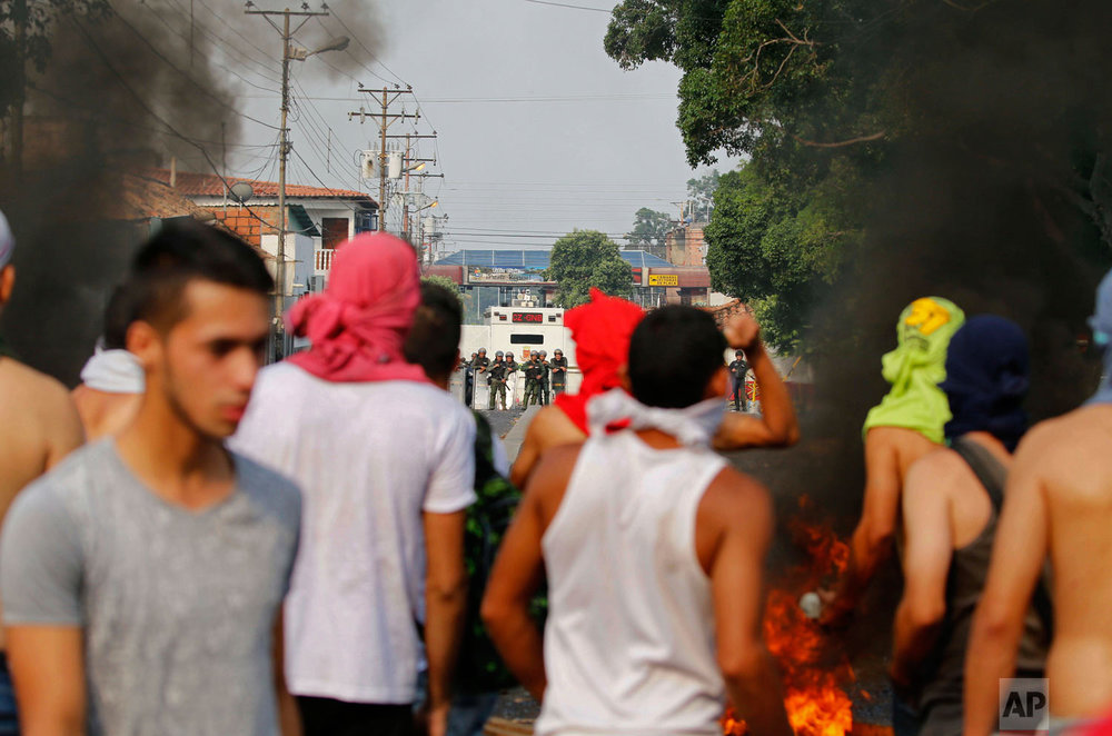 Opposition protesters face off with Venezuelan Bolivarian National Guards in Urena, Venezuela, near the border with Colombia, Saturday, Feb. 23, 2019. (AP Photo/Fernando Llano)