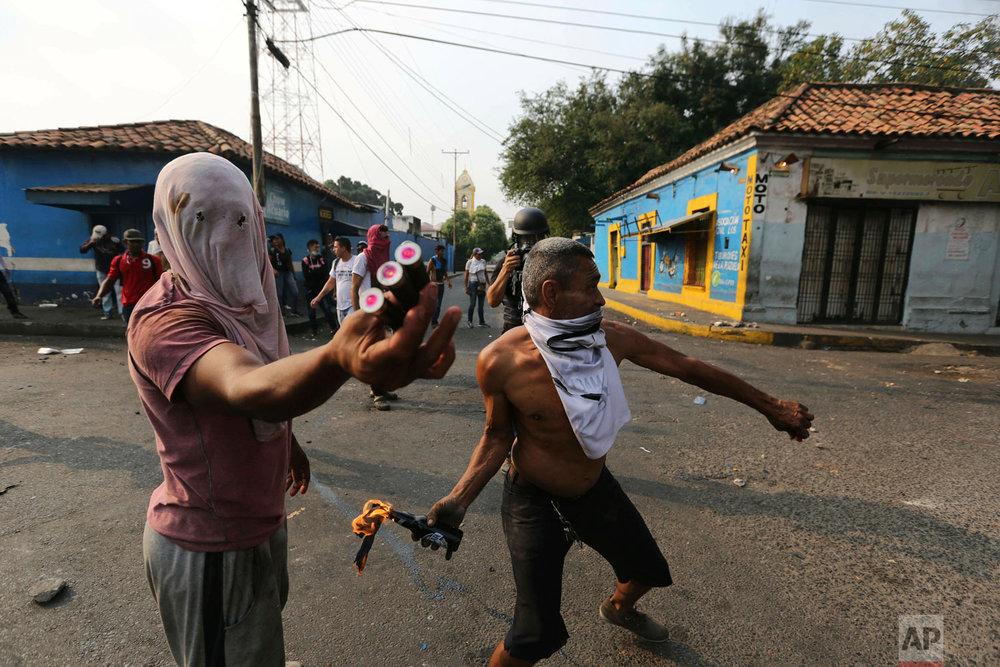 Opposition demonstrators clash with the Venezuelan Bolivarian National Guards in Urena, Venezuela, near the border with Colombia, Saturday, Feb. 23, 2019. (AP Photo/Fernando Llano)
