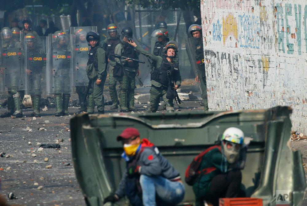 A Venezuelan Bolivarian National Guard officer throws a teargas grenade at demonstrators in Urena, Venezuela, near the bordr with Colombia, Saturday, Feb. 23, 2019. (AP Photo/Fernando Llano)