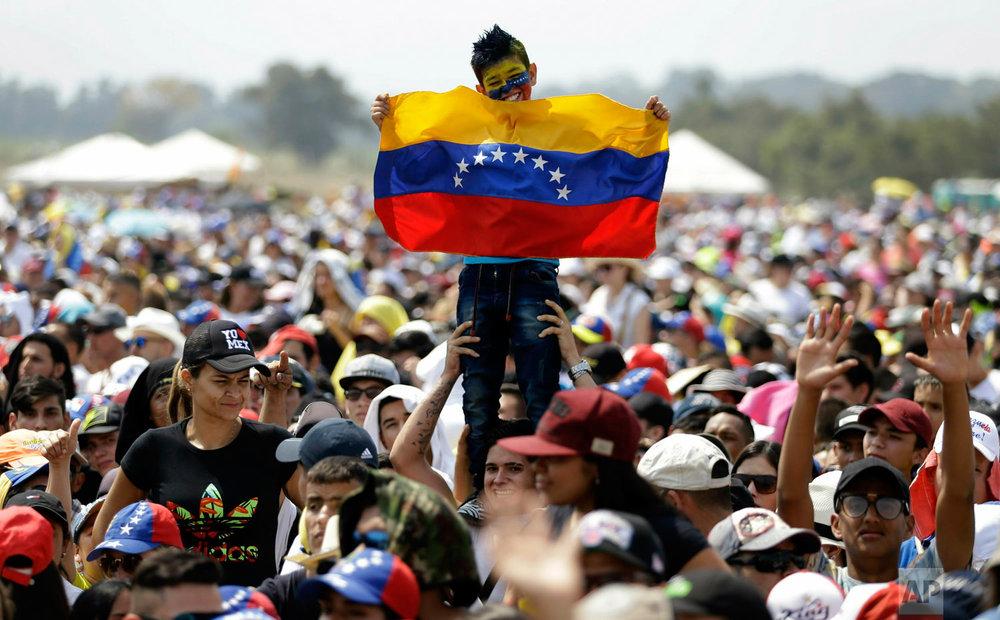 A youth holds a Venezuelan flag during the Venezuela Aid Live concert on the Colombian side of Tienditas International Bridge on the outskirts of Cucuta, Colombia, on the border with Venezuela, Friday, Feb. 22, 2019. (AP Photo/Fernando Vergara)